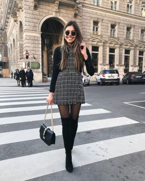 Slim girl with loose brown hair in a black suit with white squares, black stockings and greasy high boots