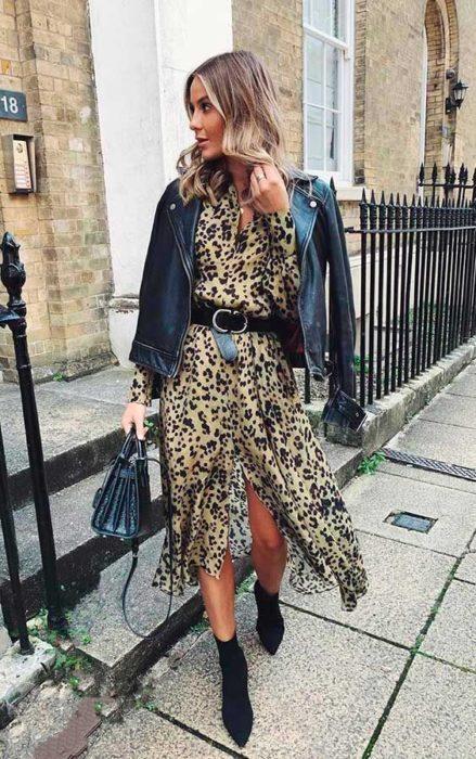 Chica rubia de cabello ondulado con vestido de animal print y chaqueta de cuero