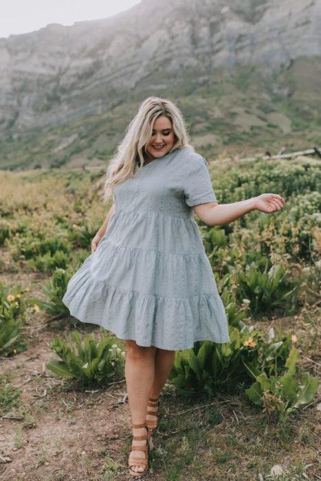 Chica plus size rubia de cabello largo y ondulado con vestido azul celeste con vuelo