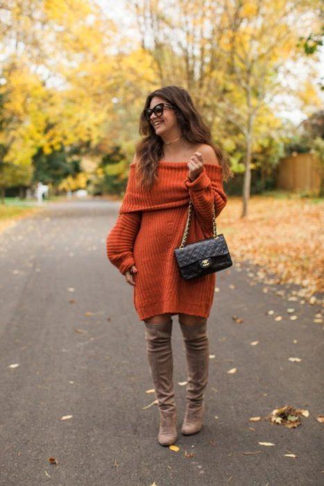 Chica de cabello castaño largo con vestido naranja largo y botas cafés