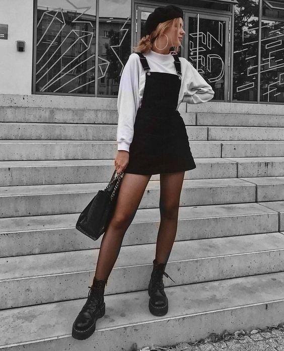 Loose blonde girl posing in black corduroy dress with white sweatshirt indoors