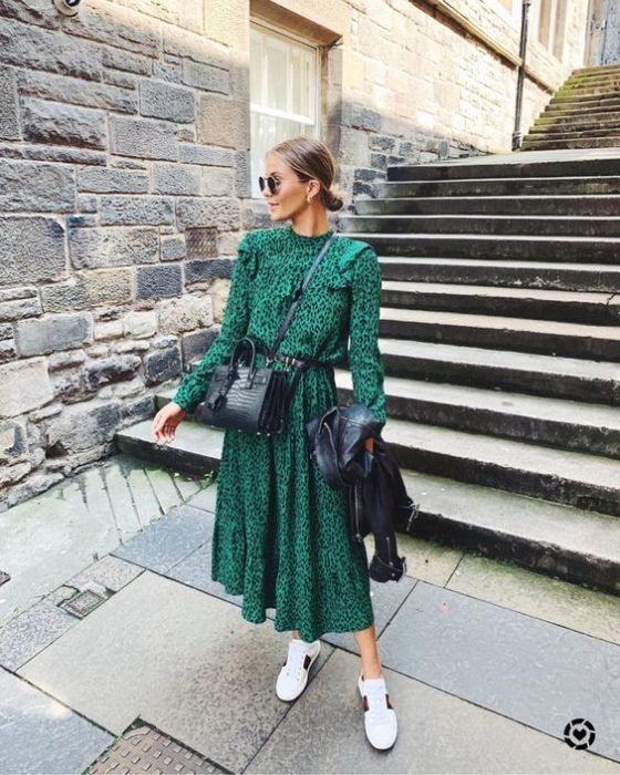 Blonde girl with hair in a low bun and long green dress with white tennis shoes