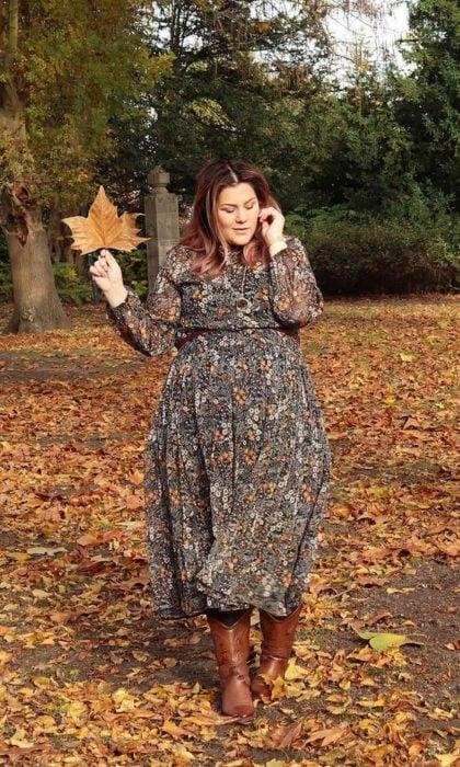 Chica plus size con vestido de chifón largo de flores posando en hojas amarillas caídas