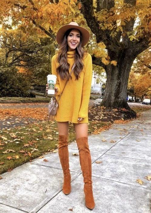 Chica delgada de cabello largo y ondulado con vestido amarillo de manga larga y cuello de tortuga con botas color camel y un sombrero