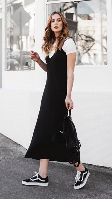 Slim blonde girl with loose hair wears long black dress with white blouse underneath
