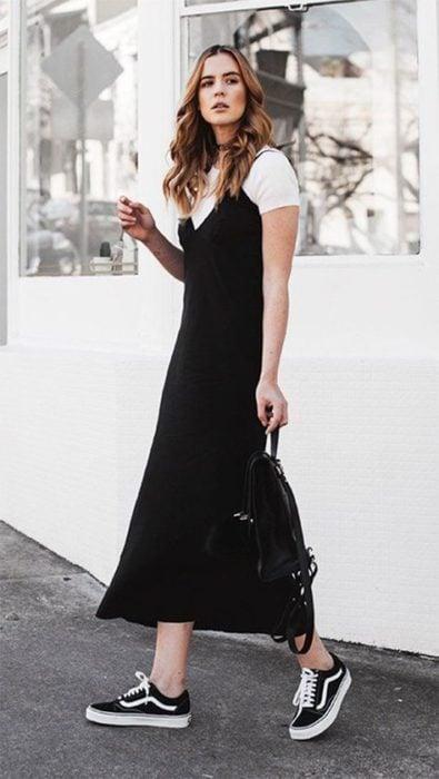Chica rubia delgada con cabello suelto viste vestido largo y negro con blusa blanca por debajo