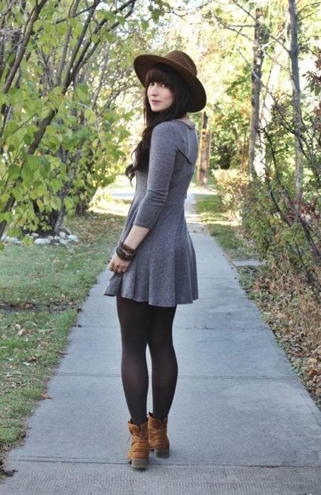 Chica delgada de cabello largo y oscuro con vestido gris y medias negras y sombrero