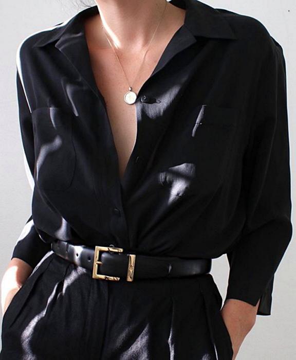 chica usando camisa negra de botones con manga larga, cinturón con hebilla dorada y pantalones de vestir negros