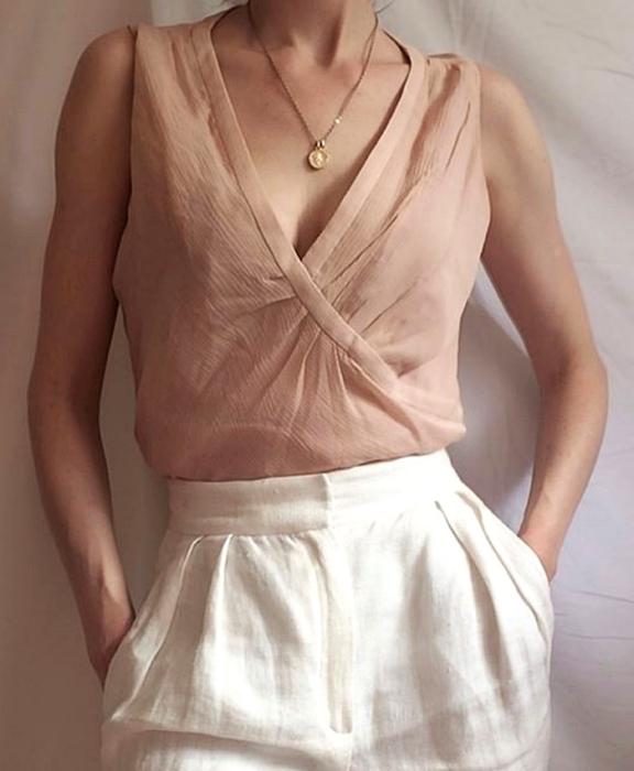 chica usando un top rosa pálido con cuello en V y pantalón de vestir blanco
