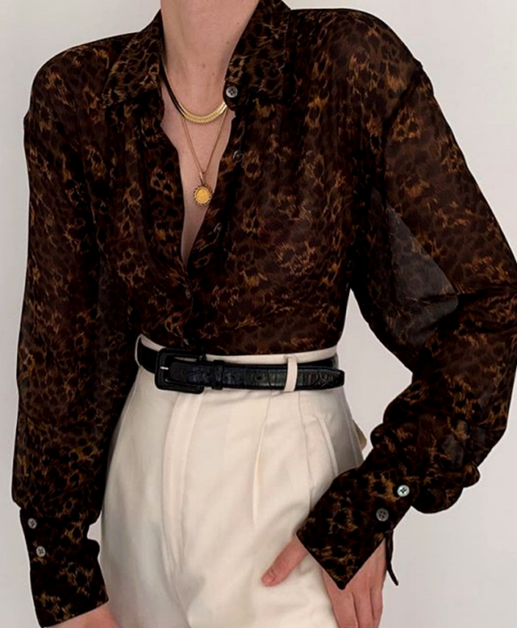 chica usando una blusa negra transparente de maga larga con cuello en V, cinturón negro y pantalón de vestir blanco