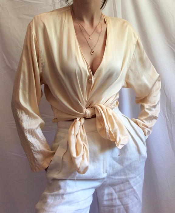 chica usando una camisa de satén beige con pantalón de vestir blanco