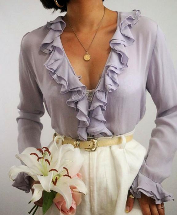 chica morena usando una blusa lila con manga larga con cuello en V y cinturón beige y pantalones de vestir blancos