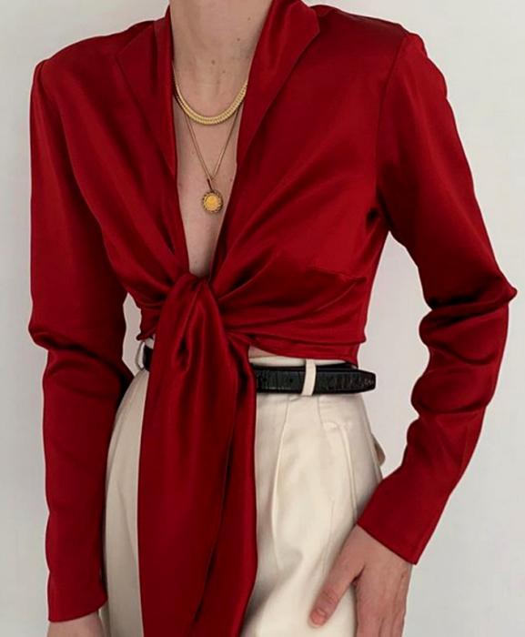 chica usando una blusa roja con cuello en V de manga larga, cinturón negro y pantalón blanco de vestir