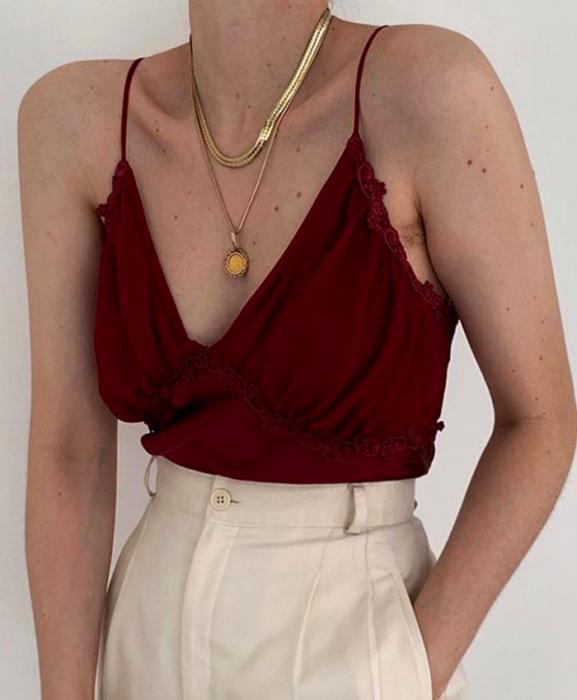 chica usando un top de tirantes color rojo intenso con pantalón de vestir blanco