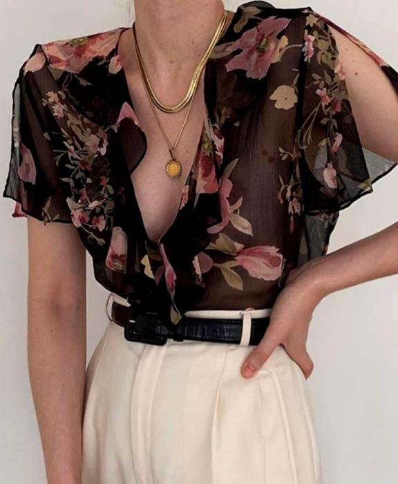 chica usando una blusa negra semi transparente con flores rosas, cinturón negro y pantalón blanco
