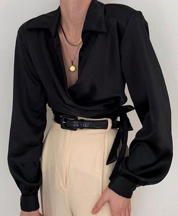 chica usando una blusa de satén color negro con cinturón negro y pantalones de vestir blancos