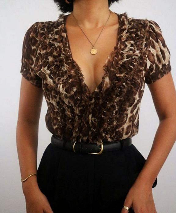 chica morena usando una blusa de animal print con escote de cuello en V, cinturón negro con hebilla dorada y pantalón negro de vestir