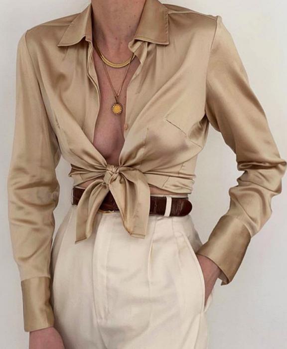 chica usando una blusa de botones de satén color beige con cinturón café y pantalón de vestir blanco