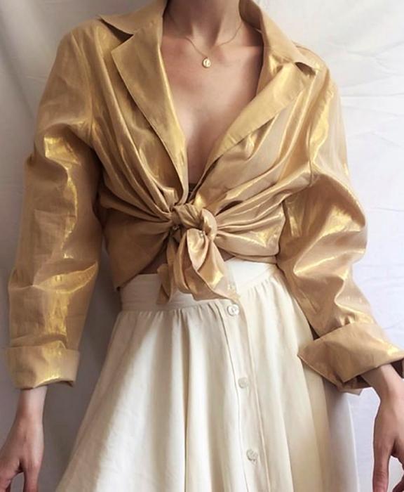 chica usando camisa dorada de botones con cuello en V y falda beige larga