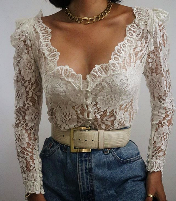 white lace blouse with long sleeves, v-neckline, white leather belt, jeans at the waist and gold link necklace