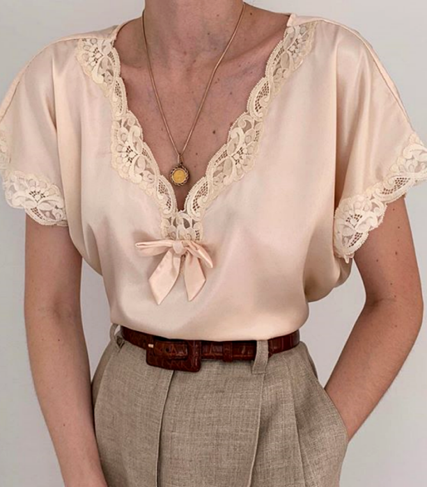 beige strapless blouse with v-neck lace and short sleeves, brown belt and beige dress pants at the waist