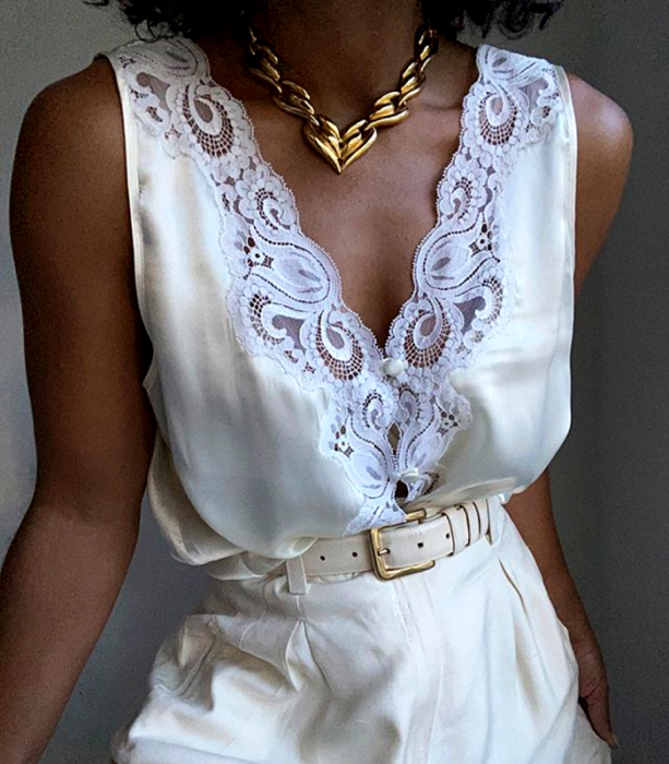 White V neck sleeveless blouse with lace, white belt, white waist dress pants and gold link necklace
