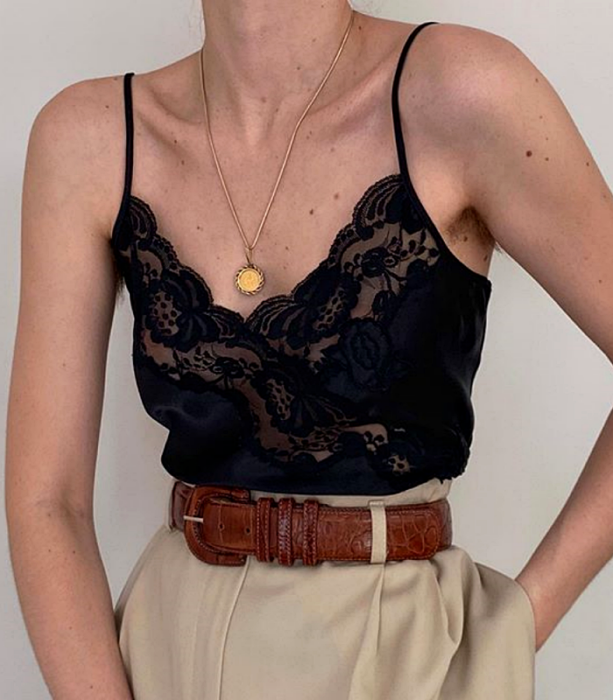 Black blouse with straps with black lace crossed v-neckline, brown leather belt, beige dress pants at the waist and gold necklace with a medal
