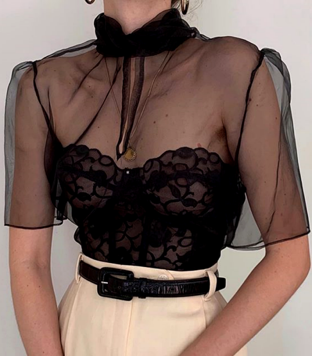 black organza blouse with black lace corset, short sleeves and high neck with cream colored dress pants at the waist with black leather belt