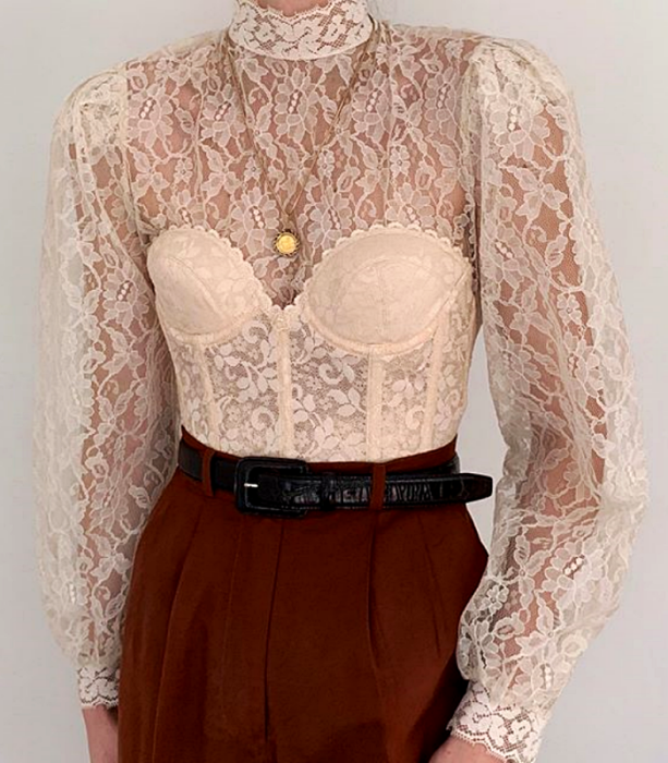 cream high neck long sleeve lace blouse with beige lace corset with black leather belt and dark orange dress pants