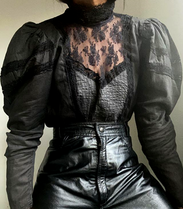 Black lace blouse with long sleeves and high neck, puff sleeves and leather pants at the waist