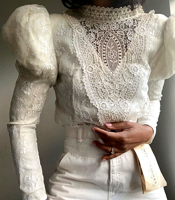 white lace blouse, long sleeves, high neck and puffed shoulders, white jeans at the waist