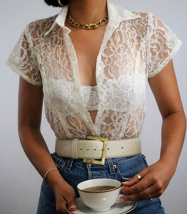 White lace button-down shirt with short sleeves and dress collar, white leather belt, jeans at the waist and gold link necklace