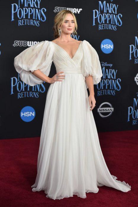 Emily Blunt en la alfombra roja de Mary Popyns usando un vestido de color blanco