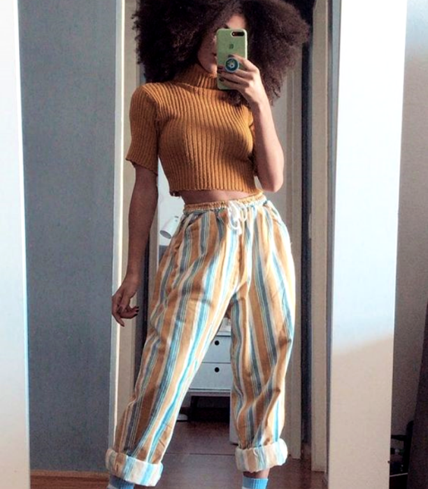 brunette girl with orange t-shirt and white, yellow and light blue striped pants