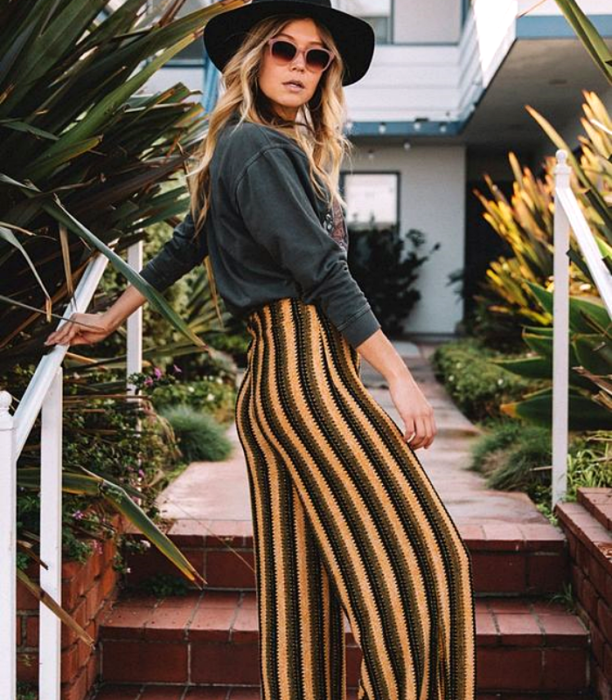 blonde girl in hat, sunglasses, gray long sleeve top with yellow, green and black striped pants
