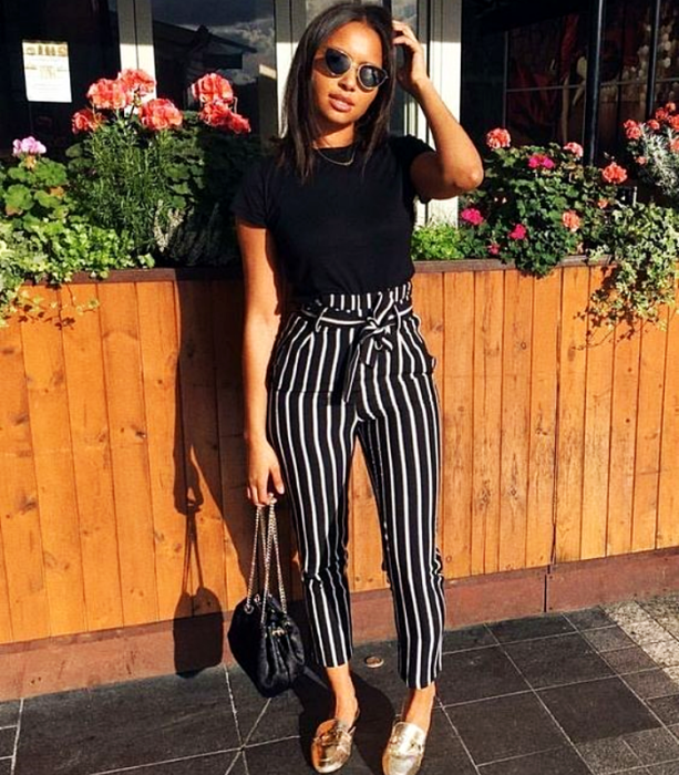 brunette girl wearing sunglasses, black t-shirt and black striped pants with white and gold flats