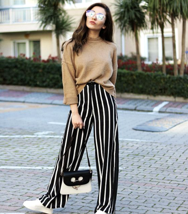 brown-haired girl wearing sunglasses, beige sweater, black pants with white stripes and white sports sneakers