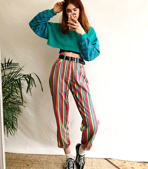 red-haired girl wearing a long-sleeved green crop top with blue lines, yellow, green, red, and white striped pants with black sports tennis shoes