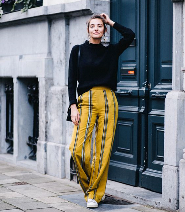 brown haired girl wearing black sweater with yellow pants with blue stripes with white