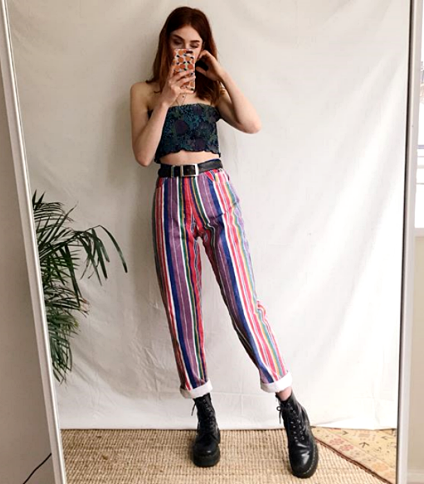 redhead girl wearing a green crop top and pink, blue, white and purple striped pants with black ankle boots