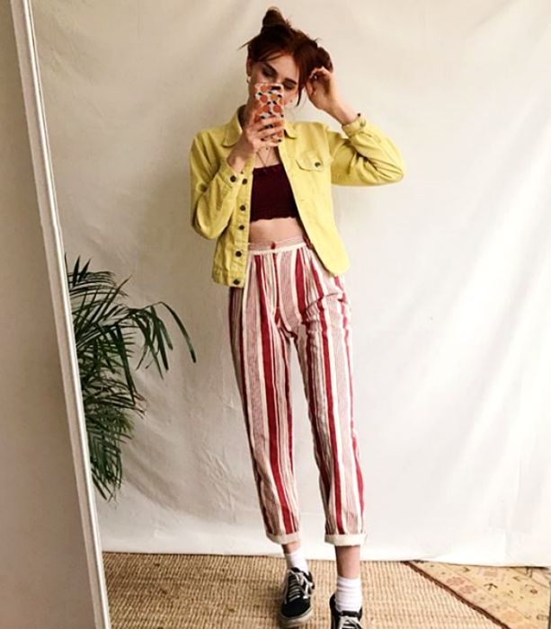 redhead girl wearing a yellow jacket, cherry crop top, red with white and pink striped pants and sports sneakers