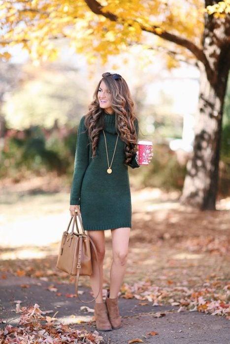 Chica delgada de cabello castaño ondulado sosteniendo un café y con vestido verde de punto y bolsa de mano café