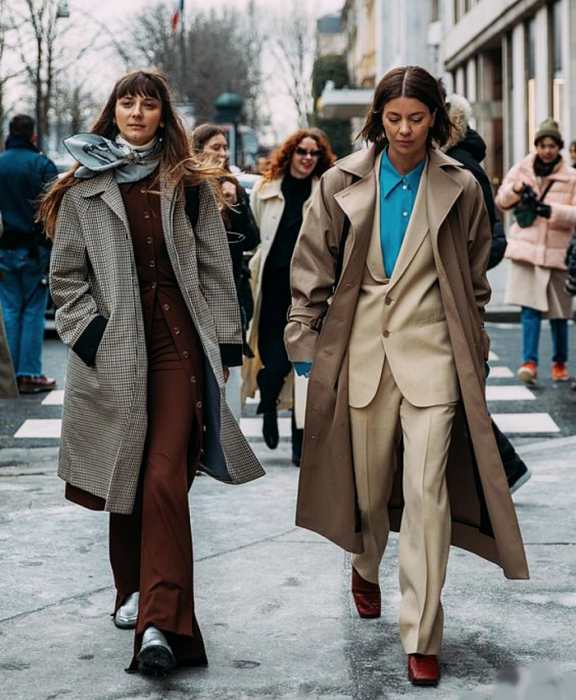 brown haired girl wearing a blue scarf, white turtleneck top, brown jacket, brown dress pants, long white plaid coat and silver ankle boots, short haired girl wearing a blue dress shirt, beige jacket, beige dress pants and long brown coat, brown square-toe ankle boots