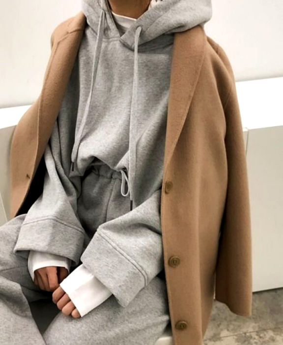 girl wearing oversized gray sweatshirt, oversized gray sweatpants, long sleeve white top underneath and long beige corduroy coat