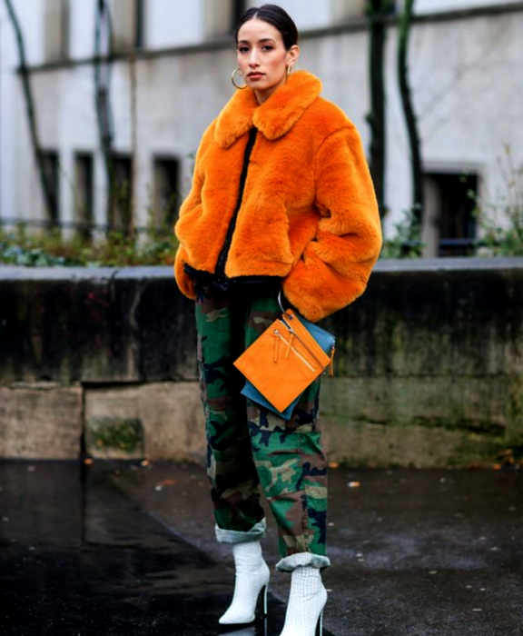 brown haired girl wearing orange teddy coat, black jacket underneath, camouflage pants, white high heel ankle boots and orange clutch bag