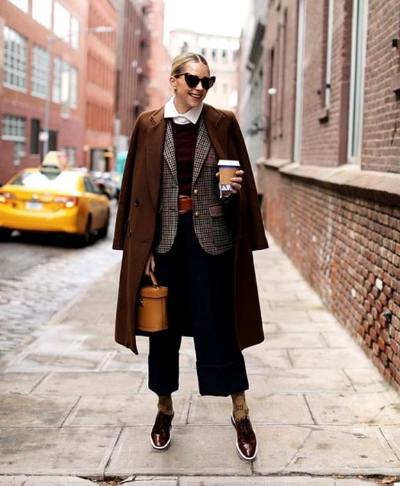 blonde girl wearing heart shaped sunglasses, collared dress shirt, navy blue sweater, brown belt, brown checked jacket, long brown coat, black dress pants, brown socks, brown dress shoes, orange bucket bag