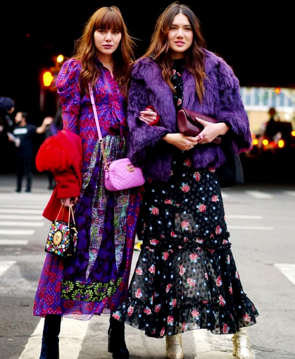 brown haired girl wearing purple dress printed with red flowers and tribal shapes, black velvet ankle boots, pink handbag and black handbag with colored polka dots, red coat. brown haired girl wearing black rose print dress, gold ankle boots, purple clutch bag