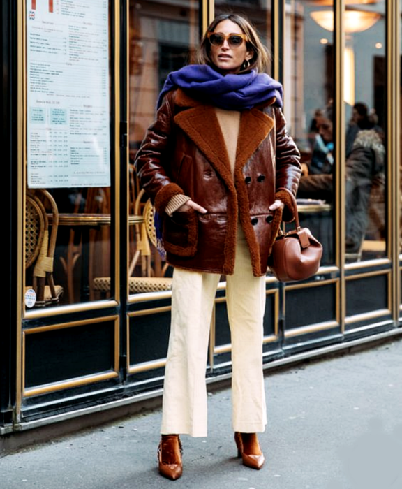 brown haired girl wearing sunglasses, purple scarf, brown leather coat, beige top, white pants, brown socks and brown leather heels, brown handbag