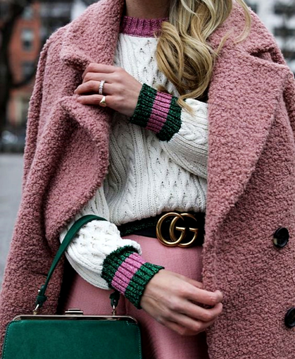 blonde girl wearing white sweater with pink collar and green cuffs with pink, black belt, pink skirt, pink teddy coat and green clutch bag