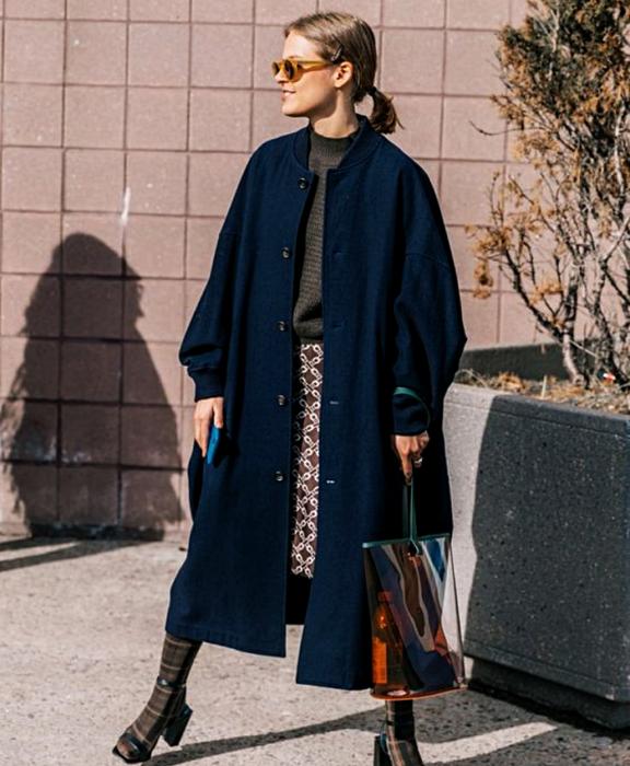 blonde girl wearing sunglasses, navy coat, dark gray sweater, plaid print skirt, transparent bag, brown socks and navy blue heels